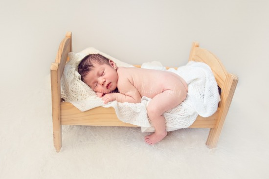 Baby on photography prop bed
